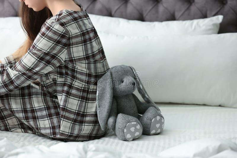Umkippenjugendliche mit dem Spielzeug, das auf Bett sitzt lizenzfreies stockfoto