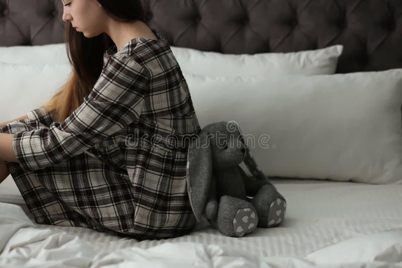 Umkippenjugendliche mit dem Spielzeug, das auf Bett sitzt lizenzfreies stockbild