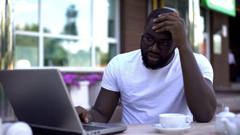 Umkippenmann, der den Laptop, enttäuscht über verlorene Finanzierung nach Anfang oben, Ausfallung betrachtet lizenzfreie stockfotografie
