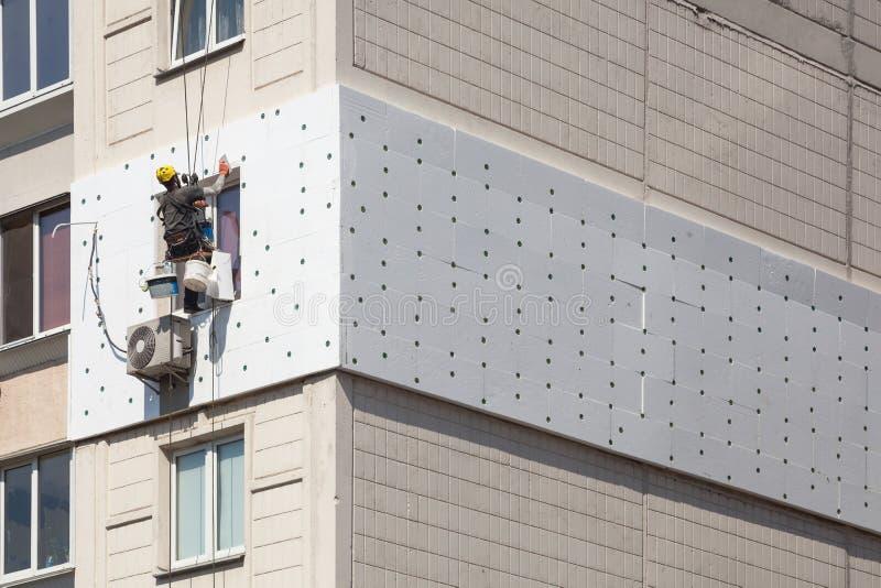 Ummauern Sie Wärmedämmung, das industrielle Klettern, hoch gelegene Arbeit, Isolierung von Wänden mit Schaumstoff oder Styroschau lizenzfreie stockbilder