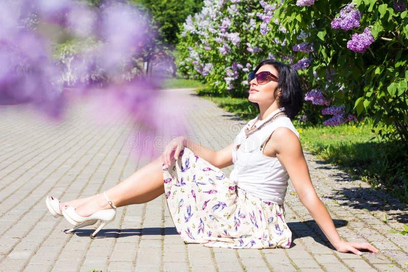 Umore di estate Donna con i fiori Una donna sta sedendosi sulla pavimentazione fra i lillà fotografia stock libera da diritti