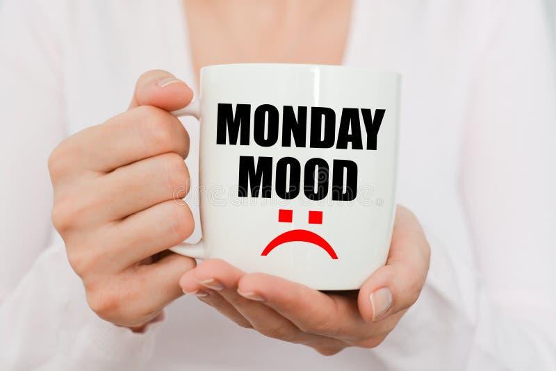 Umore di lunedì con il simbolo triste sulla tazza di caffè macchiato immagini stock