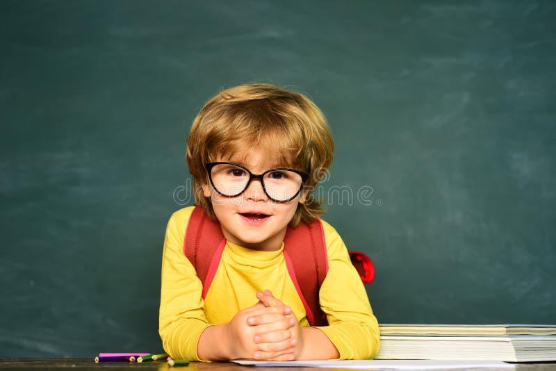 Umore felice che sorride largamente a scuola Ragazzino divertente che indica su sulla lavagna Di nuovo al banco Banco e formazion immagine stock libera da diritti