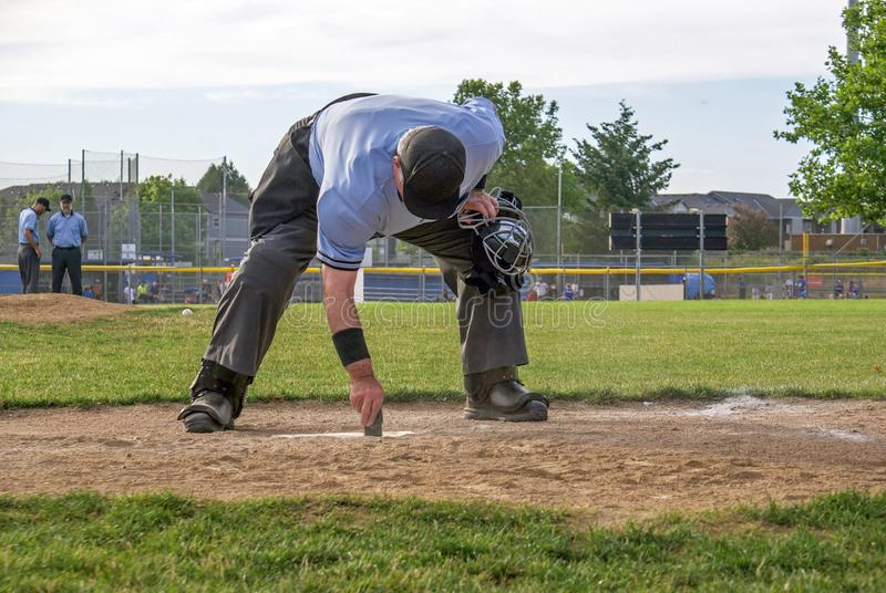 Umpire cleaning home plate stock photography