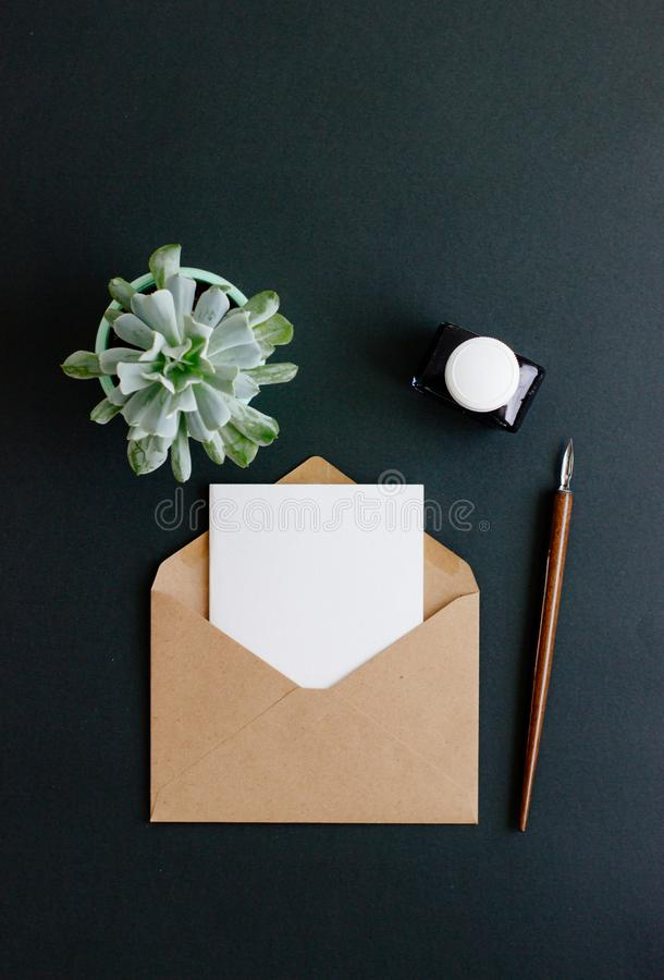 Umschlag, Füllfederhalter und Tintenfaß sind auf einem schwarzen Hintergrund stockbild