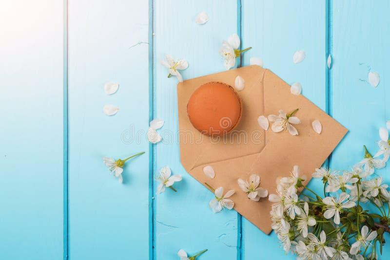 Umschlag mit Frühlingsblumen und einer Makrone auf blauem hölzernem lizenzfreie stockfotografie