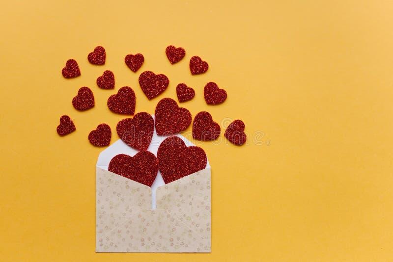 Umschlag mit Symbolen in Form von roten Herzen auf einem gelben Hintergrund feier stockfotos