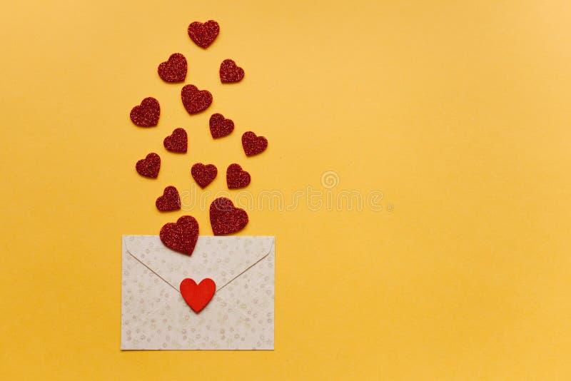 Umschlag mit Symbolen in Form von roten Herzen auf einem gelben Hintergrund feier lizenzfreies stockbild