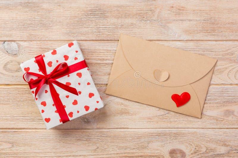 Umschlag-Post mit rotem Herzen und Geschenkbox über orange hölzernem Hintergrund Valentine Day Card-, Liebes-oder Hochzeits-Gruß- stockbilder