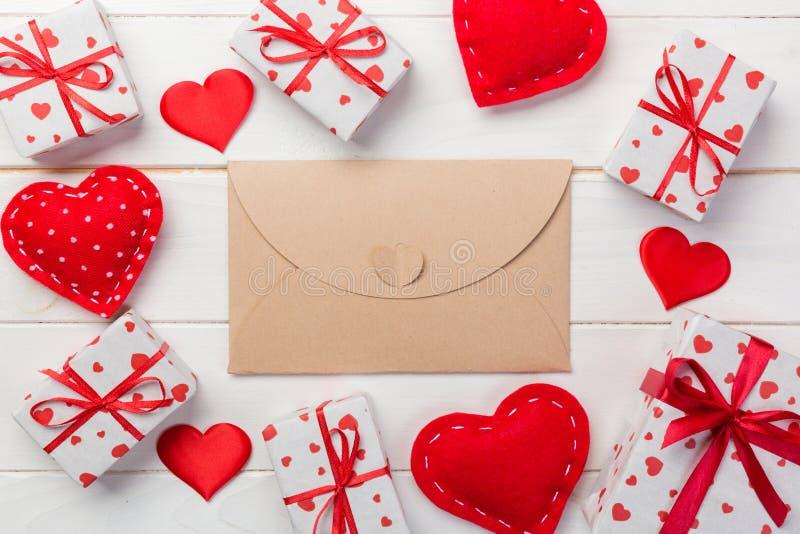 Umschlag-Post mit rotem Herzen und Geschenkbox über weißem hölzernem Hintergrund Valentine Day Card-, Liebes-oder Hochzeits-Gruß- stockbilder