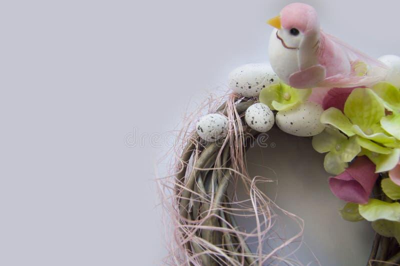 Umsponnener Kranz mit Ostereiern auf grauem Hintergrund stockfotografie