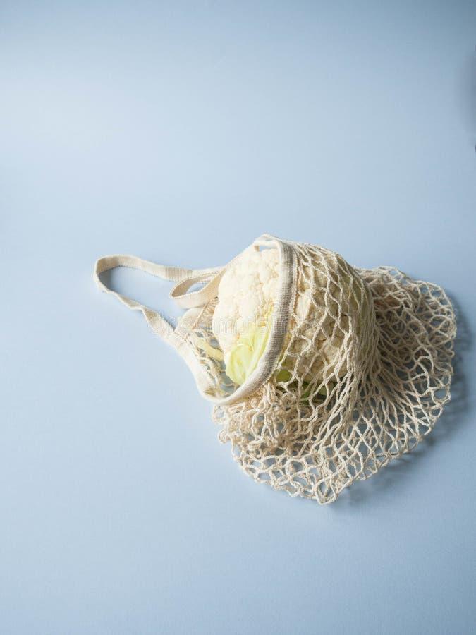 Umweltfreundliche beige Einkaufstasche mit Blumenkohl auf einem blauen Hintergrund Einkaufsnetz mit Gemüse Nullabfall, kein Plast lizenzfreie stockfotografie