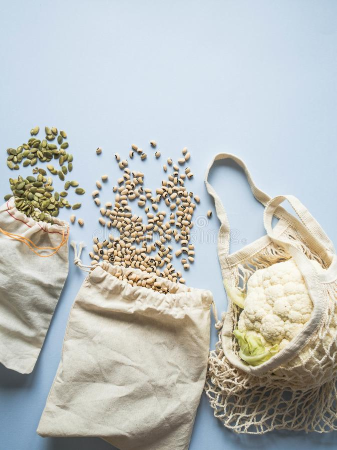 Umweltfreundliche beige Einkaufstaschen mit Blumenkohl, Bohnen, Kürbiskerne auf einem blauen Hintergrund Einkaufsnetz mit Gemüse  stockbilder