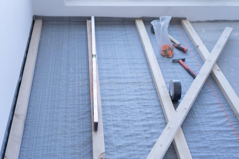 Umweltfreundlichen hölzernen Bodenbelag legen - Installation eines Protokollierunges in Beton lizenzfreies stockfoto