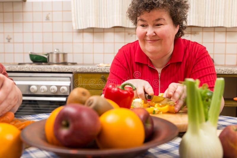 Umysłowo - niepełnosprawna kobieta uczy się kucharstwo w kuchni fotografia royalty free