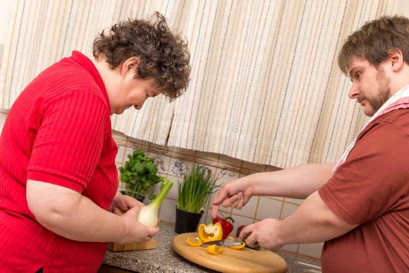 Umysłowo - niepełnosprawna kobieta uczy się kucharstwo w kuchni obraz royalty free