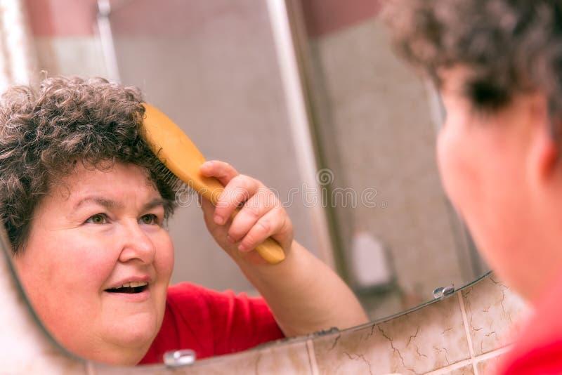 Umysłowo - niepełnosprawny kobiety czesanie przez jej włosy zdjęcie stock
