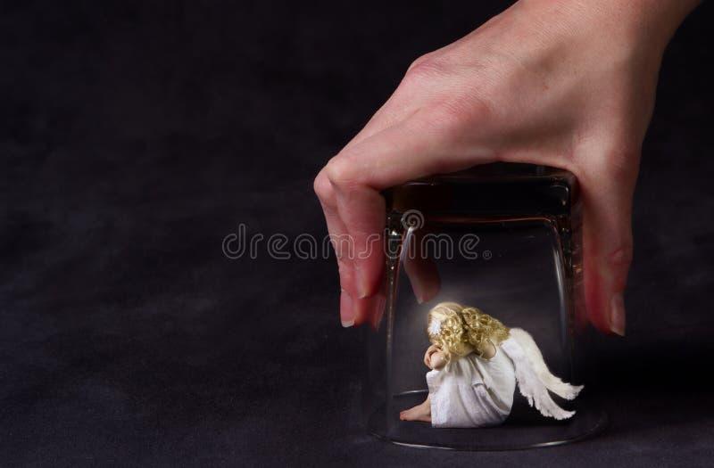Un ángel atrapado bajo un vidrio imagen de archivo libre de regalías