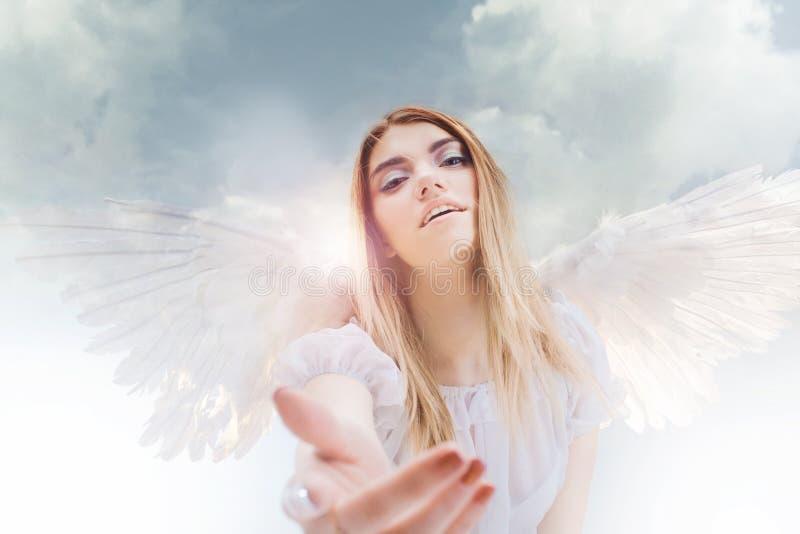 Un ángel del cielo le da una mano Jóvenes, muchacha rubia maravillosa en la imagen de un ángel con las alas blancas imagen de archivo libre de regalías