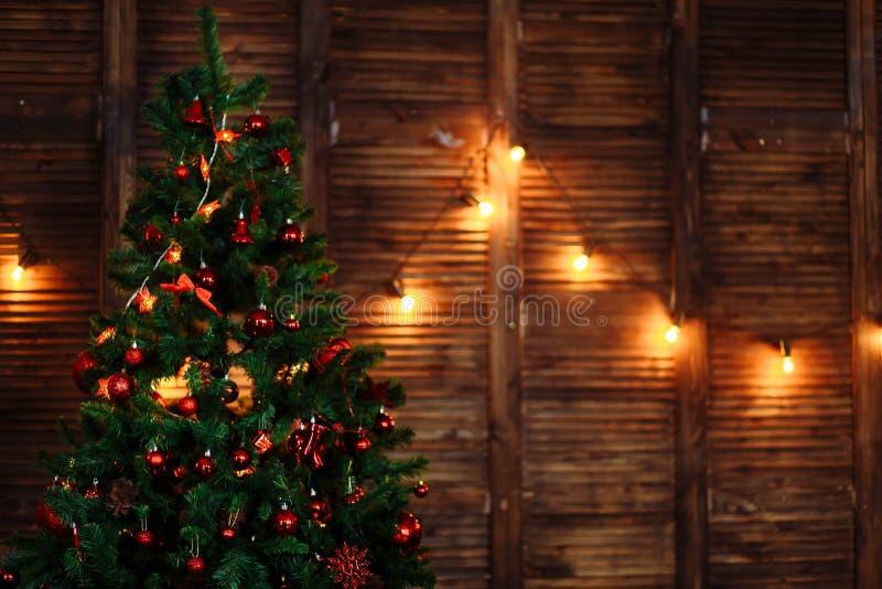 Un árbol de navidad adornado con los juguetes adorna la guirnalda roja de las gotas en copyspace marrón de madera de la pared imagenes de archivo