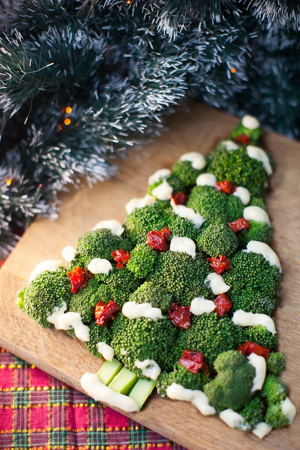 Un árbol verde del bróculi con los tomates en un tablero de madera imágenes de archivo libres de regalías