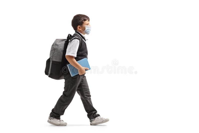Un écolier avec un sac à dos qui marche et porte un masque de protection image stock