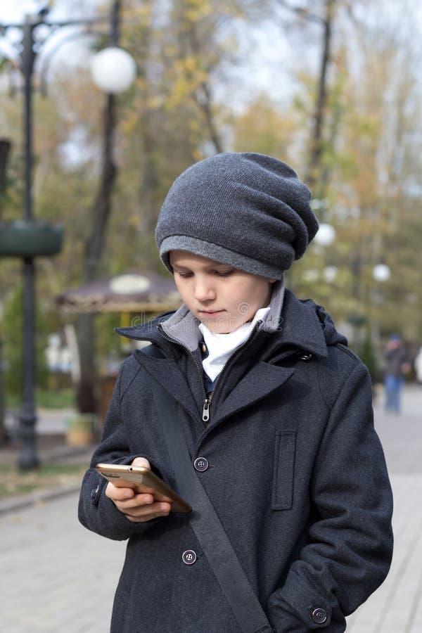 Un écolier en chapeau tenant un smartphone à la main et un numéro de téléphone sur écran tactile L'extérieur dans le parc Journée image stock
