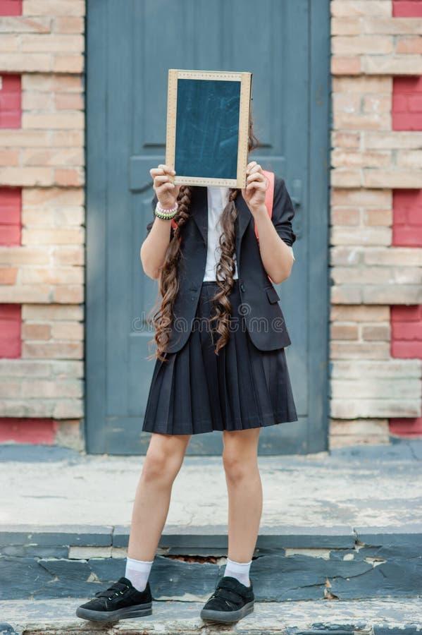Un écolier tenant un panneau de craie photographie stock