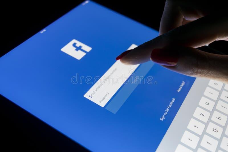 Un écran tactile de main du ` s de femme sur l'iPad d'Apple pro la nuit avec la page Web de page d'accueil de Facebook Facebook l image libre de droits