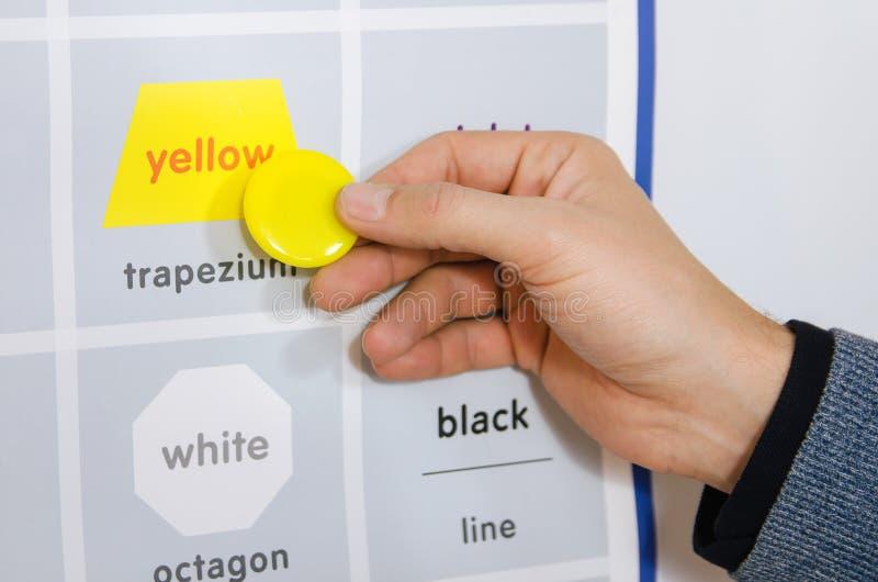 Un éducateur explique l'orthographe du jaune de mot photographie stock