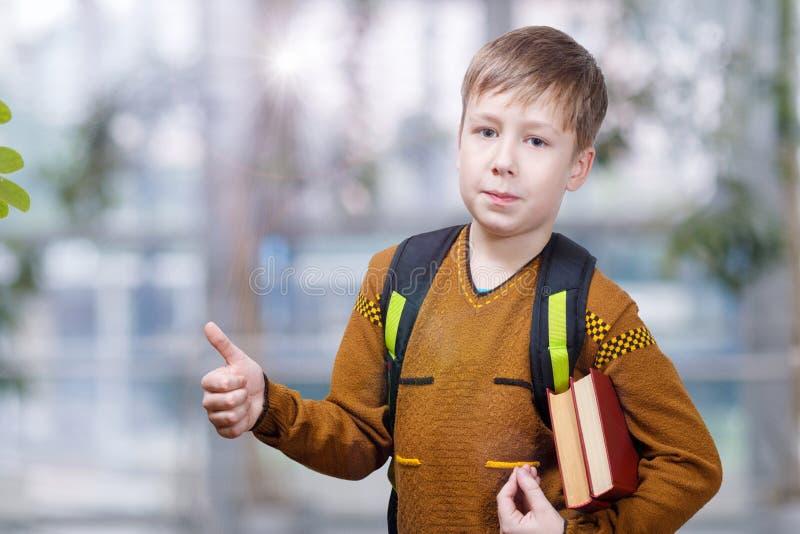 Un élève avec le sac d'école et manuels montrant un geste positif photos libres de droits