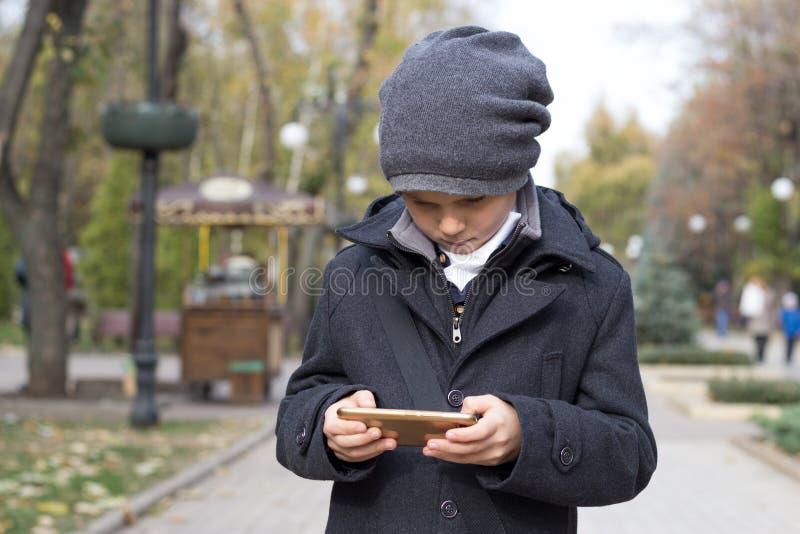 Un élève du primaire joue avec enthousiasme sur son smartphone, le tenant dans les deux mains Animation de photos libres de droits