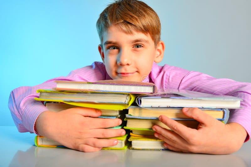 Un étudiant a étreint des manuels avec ses mains, amours joyeux d'un écolier pour apprendre images libres de droits