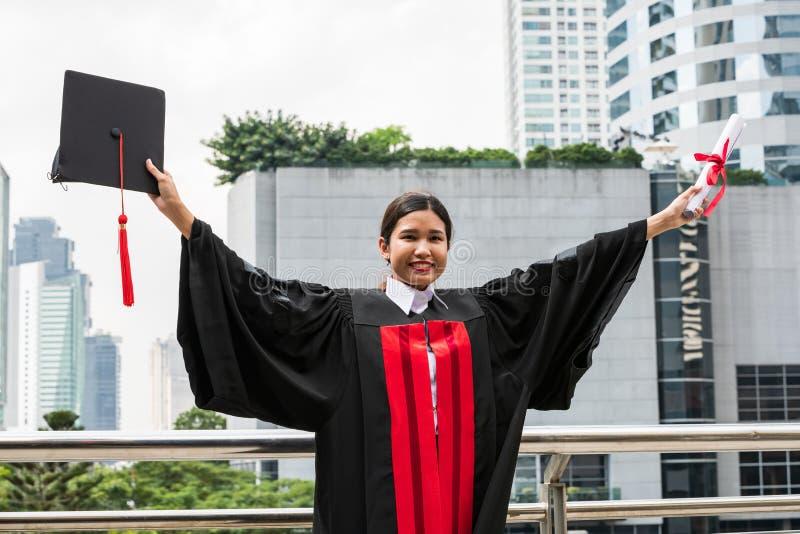 Un étudiant asiatique féminin dans la robe d'obtention du diplôme jugeant le diplôme photos stock