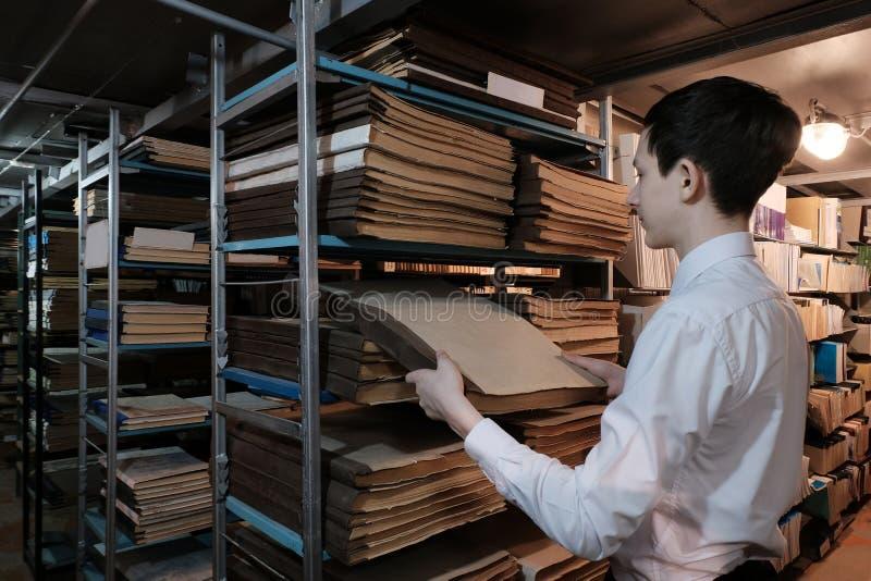 Un étudiant dans la bibliothèque ou dans la salle d'archives recherche l'information Un écolier dans une chemise blanche retire u photographie stock