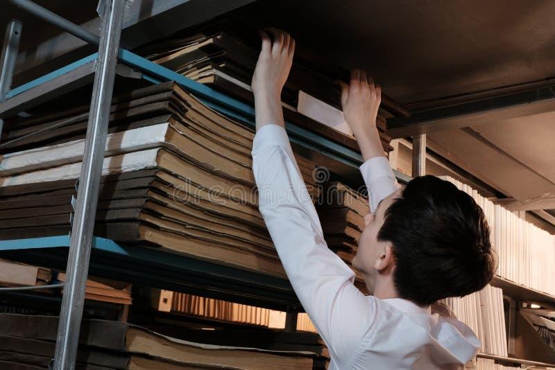 Un étudiant dans une chemise blanche retire un vieux livre de l'étagère supérieure dans la bibliothèque ou dans la salle d'archiv photos libres de droits