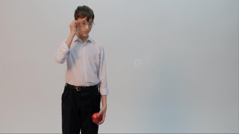 Un étudiant habillé dans une chemise blanche et un pantalon noir tient une pomme dans une main, alors que l'autre redresse ses ve photographie stock