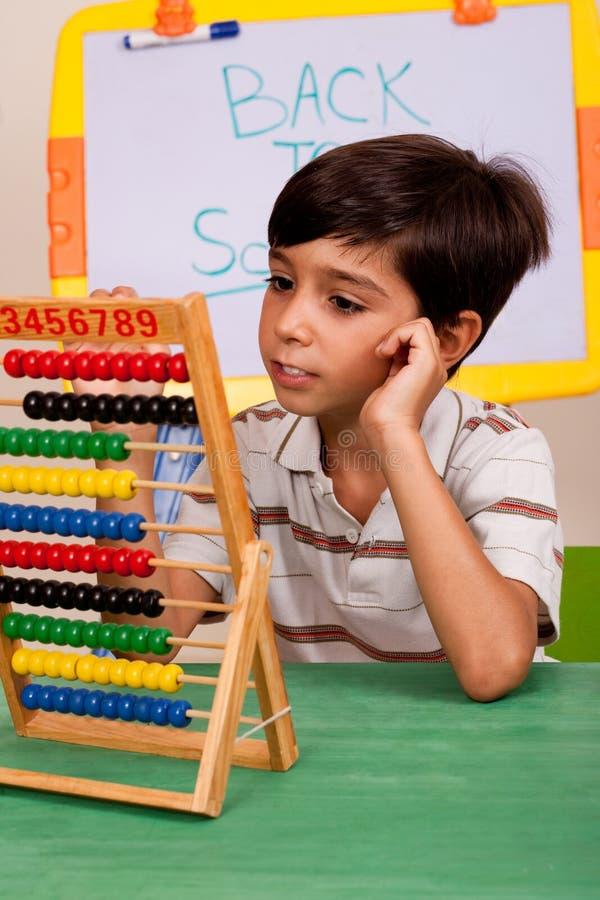 Un étudiant résolvant une affectation de maths images stock