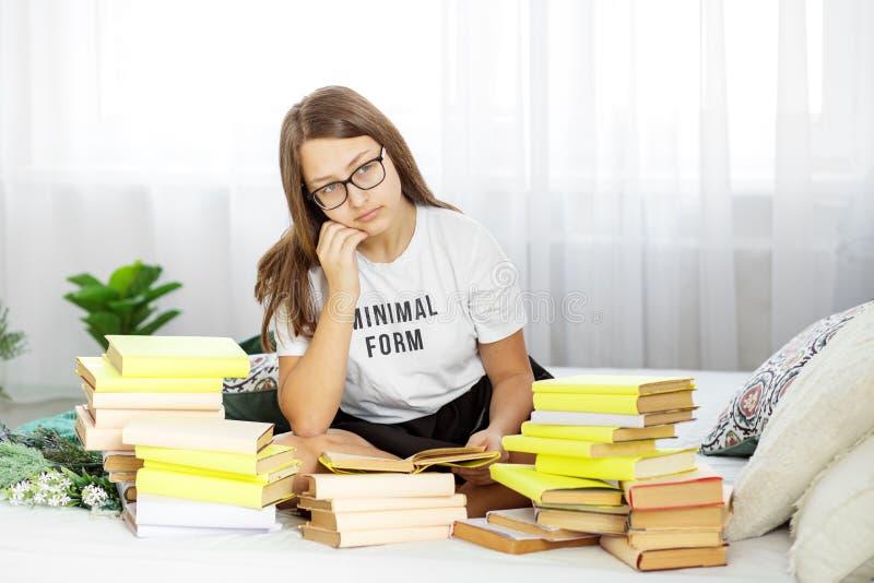Un étudiant se prépare aux examens avec des verres Beaucoup de manuels Concept d'éducation, passe-temps et étude et jour de livre photographie stock