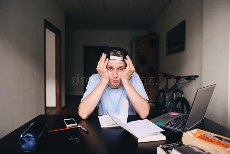 Un étudiant triste s'asseyant à un bureau de travail à une maison près d'un ordinateur portable et des livres Enseignement à la m image libre de droits
