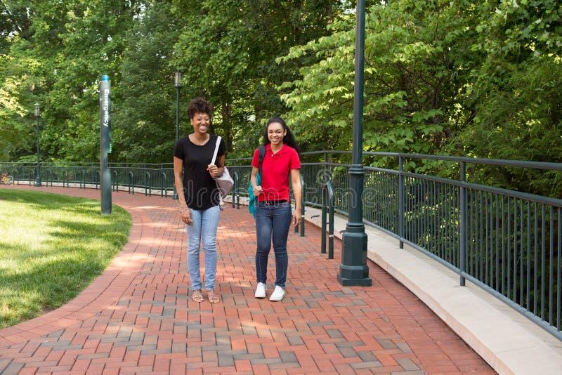 Un étudiant universitaire marchant sur le campus image stock