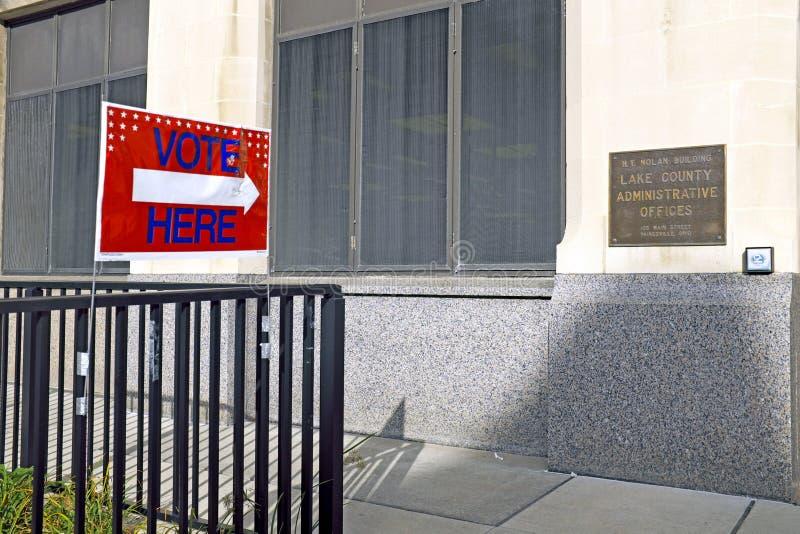 """Un """"vote ici """"fixé à une barrière en dehors du conseil du comté de Lake Ohio des élections construisant dans Painesville, Ohio photo stock"""