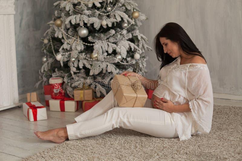 Un Año Nuevo de los regalos de Navidad de la entrega de la mujer embarazada imagen de archivo libre de regalías