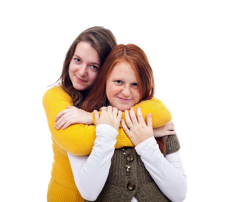 Un abbraccio di due amiche dell'adolescente immagine stock libera da diritti