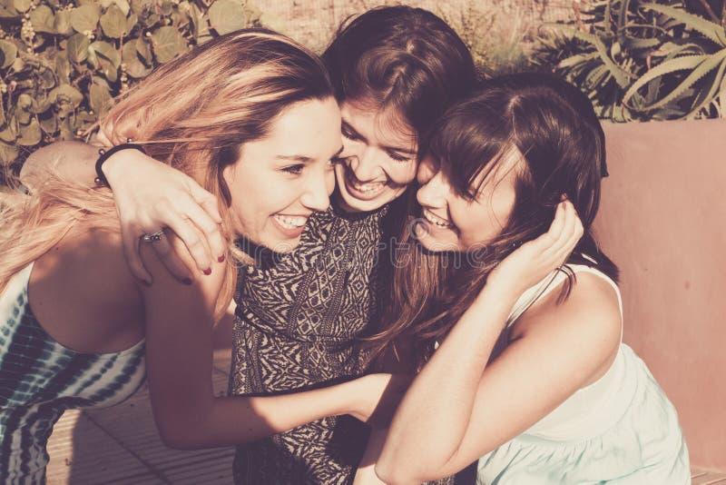 Un abbraccio stessi di tre giovani donne in un giorno soleggiato fotografia stock libera da diritti