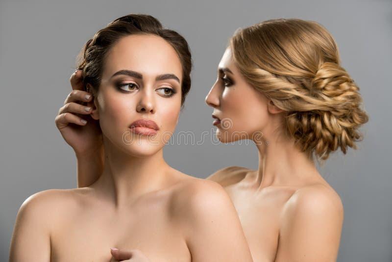 Un abbraccio topless di due modelli tenero in studio fotografia stock