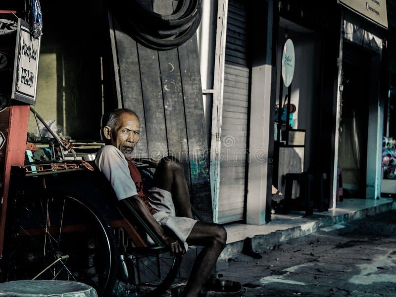 Un abuelo que está descansando mientras que espera a un pasajero fotografía de archivo