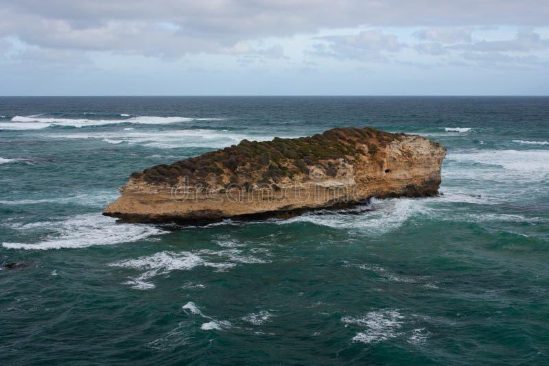Un acantilado en el medio del mar lavado por las ondas en el gran camino del océano en Australia foto de archivo