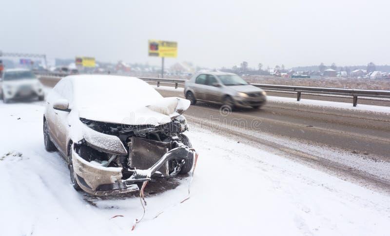 Un accident avec une voiture blanche en hiver sur la route, route glaciale glissante, entraînement de danger image stock