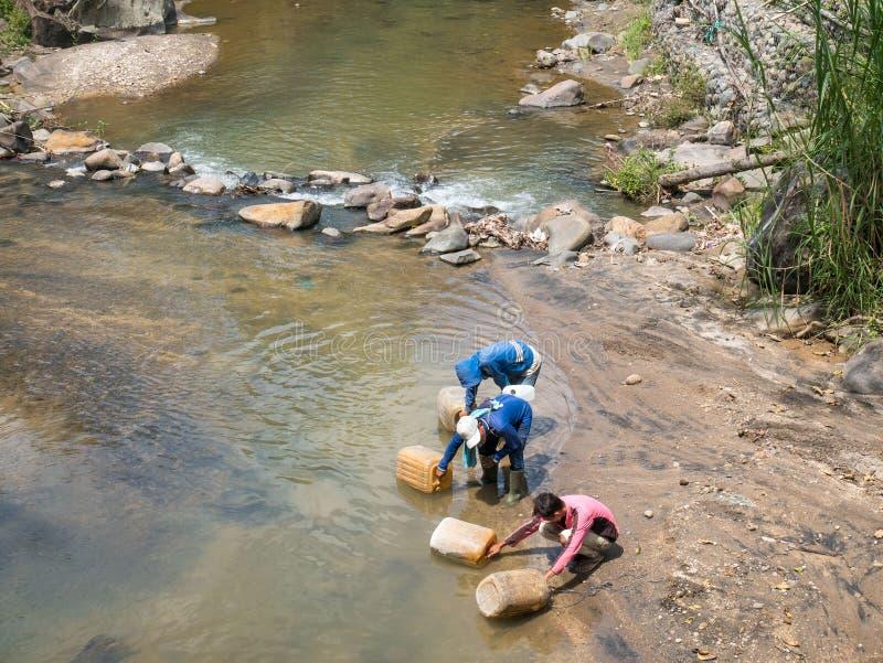 Un'acqua di riempimento di tre uomini in Jerry Can nel fiume fotografie stock libere da diritti